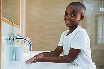 A young boy washes his hands with soap and water