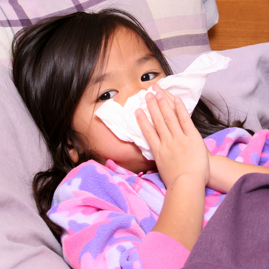 Child blowing her nose, sick in bed with a cold.
